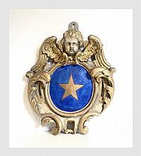 Elément de décoration en bois doré sculpté de feuilles d'acanthe et d'un ange à la partie supérieure. Il est décoré d'une étoile à 5 branches dans un fond bleau en son centre. XVIIIème siècle. H : 57 cm L : 45 cm