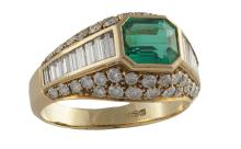 An Emerald and Diamond RingThe collet-set emerald, within a baguette-cut and brilliant-cut diamond surround, mounted in 18K gold, diamonds approximately 1.60cts total, ring size J