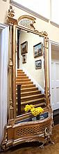 A 19TH CENTURY FRENCH GILTWOOD STANDING MIRROR with arched asymmetrical top