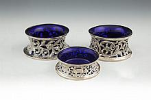 TWO SIMILAR IRISH SILVER SMALL DISH RINGS, Dublin 1906 & 1919, mark of Edmond Johnson, with pierced, chased and engraved repoussé foliate and scroll decoration (c.8oz). 12cm and 12.5cm diameter; together with a compressed circular dish ring, Dublin 1