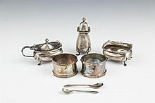 A CASED SET OF SILVER CONDIMENTS, Birmingham, comprising - an open salt cellar- a pepper pot- and a mustard pot, each in georgian style;together with a cased pair of celtic revival silver napkin rings, Birmingham.