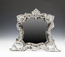 A LARGE EDWARDIAN SILVER DRESSING TABLE MIRROR, London 1903, mark of William Comyns & Sons Ltd., of shaped waisted form, decorated in the Rococo style with chased rockwork and oppossing 'c' scrolls, headed by a vacant cartouche and set to each corner