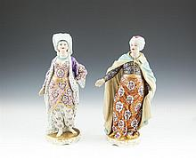 A PAIR OF ENGLISH EARLY 19TH CENTURY PORCELAIN FIGURINES MODELLED AS A SULTAN & SULTANA, each figure standing on a circular base, in richly patterned dress and turbanned, the sultan with a turquoise cape embellished with gold stars; the sultana weari