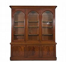 A VICTORIAN MAHOGANY BOOKCASE, the moulded cornice above three arched glazed panel doors enclosing shelves and raised on a conforming cupboard base. 221 x 260cm tall