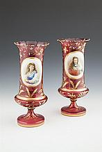 A PAIR OF VICTORIAN BOHEMIAN RUBY OVERLAID GLASS VASES, each with shaped serrated rim, the body decorated with enamel painted reserves of portraits, surrounded by foliate highlights and raised on circular spreading base. 35cm high x 15cm diameter