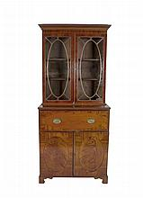 A GEORGE IV MAHOGANY SECRETAIRE BOOKCASE, the moulded cornice with a band of Greek Key decoration, above twin oval glazed doors and secretaire with cupboard base, opening to reveal a compartmented interior with fold-out baise-lined writing surface. 9