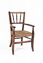 A STAINED BEECH FRAMED CHILD'S ARMCHAIR, with triple spindle back and with rush seat on splayed legs