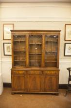 A SMALL MAHOGANY GEORGIAN STYLE BOOKCASE, the dentil cornice with plain frieze above three astragal glazed panel doors, the base with three short drawers with lion mask handles, over three cupboard drawers, raised on bracket feet. 200cm high, 146cm w