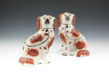 A PAIR OF LATE STAFFORDSHIRE MOULDED AND PAINTED MODELS OF SEATED DOGS. 26cm high