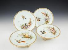 A PAIR OF ROYAL WORCESTER PORCELAIN CIRCULAR TAZZAS, and a pair of matching circular plates, the celadon green ground with floral spray, birds and insects within a gilded beaded border and raised on circular base and three scroll feet. 23.5cm diamete