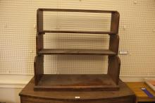 A MAHOGANY GRADUATED THREE-TIER HANGING BOOKCASE; together with a modern wine table. (2)