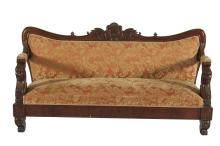 A 19TH CENTURY CONTINENTAL MAHOGANY SETTEE, the shaped back carved with central figural decoration and scrolling foliage, above upholstered panel seat, the arms carved with leaf wrapped heads and scrolls, with plain apron, raised on squat scroll feet