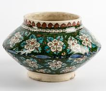 A Turkish, Kutahya Ceramic Jar, early 20th century, white flowers set in a design of branches and leaves  glazed in turquoise and green, geometric design at the opening glazed in coral, 11 x 11 x 11 cm