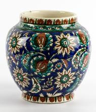 A Turkish, Kutahya Ceramic Jar, early 20th century, large intertwining palmettes and leaves glazed in coral and turquoise on a cobalt blue background with repeated leaf motif at the top and base, 20 x 12 x 13 cm