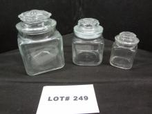 Three clear glass apothecary canisters with lids, 5