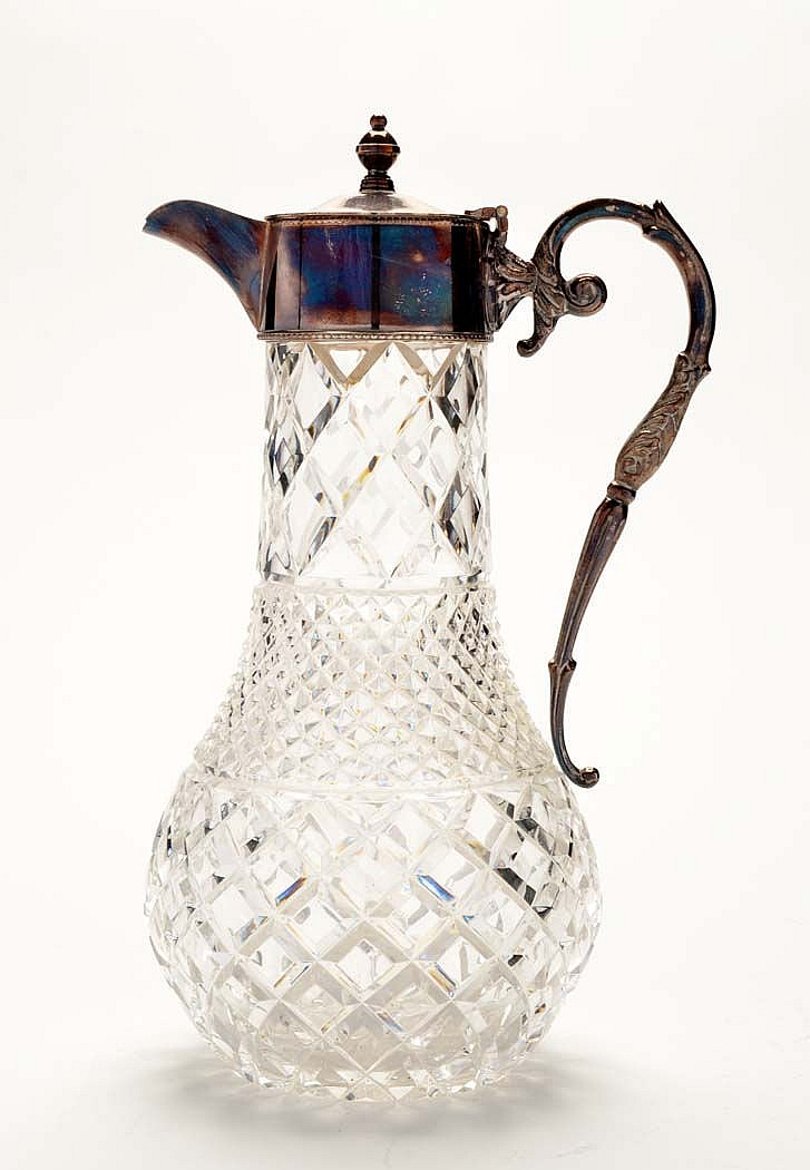 A cut glass claret jug with plated mounts and
