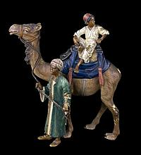 A COLD-PAINTED  BRONZE GROUP OF CAMEL WITH TWO ARABS.