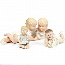 Group of four German bisque piano babies