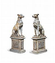 Paire de monumentaux chiens assis en marbre sculpté sur des piédestaux moulurés à panneaux de marbre gris.    Style Regency.