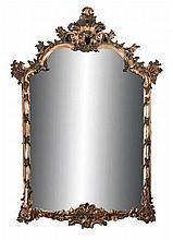 Paire d'importants miroirs en bois sculpté, argenté et partiellement polychromes.    De forme mouvementée, ils présentent un décor de feuillages, de fleurs et de branchages enroulés.