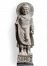 Bouddha auréolé en schiste.    Représenté debout sur une base à décor de six adorants vénérant le feu.