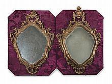 Paire de petits miroirs en bois sculpté et doré de forme mouvementée, à décor de feuillages.    Fronton ajouré de palmes et de fleurs.