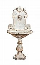 Fontaine murale en marbre blanc sculpté de feuillages.    La vasque à bandeaux alternés repose sur un pied balustre supporté par une base octogonale de marbre gris.
