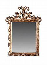 Miroir en bois sculpté et doré à décor de feuillages surmonté d'un fronton ajouré d'enroulements de palmes découpées.    Glace au mercure.