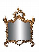 Important miroir en bois sculpté et doré de forme mouvementée, il présente un décor de feuillages découpés et de palmes.    Il est surmonté d'un fronton déchiqueté à fond de miroir.