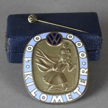 A 20th Century enamelled bronzed metal VW ?100 000 Kilometer? oval badge, with image of St Christoph