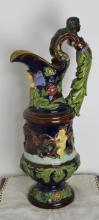 A late 19th Century German maiolica pottery jug, modelled in relief with putti astride sea creatures