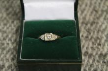 14kt gold ring with .15 carat center diamond and six small baguetts