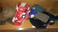Shelf lot: 13 assorted military caps incl. Russian examples, early German, Australian slouch caps etc also incl. Canadian Davey Crocker style hat together with a vintage American flag