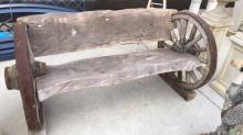 Outdoor garden bench made from wood slabs and wagon wheel ends