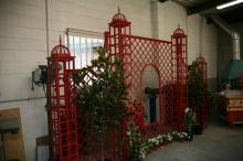 Hand forged galvanised steel, free standing garden treillage screen, painted Nepalese Red, with ornate finials to top, 4.158m wide x 2.876m high x 0.250m deep,  RRP $7000.00 Note: buyer is responsible for dismantling and transporting