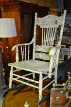 An antique wooden rocking chair, pressed back with