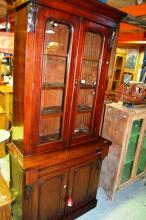 An antique Victorian bookcase, topped with pair of