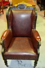 An antique, highbacked armchair, carved wooden