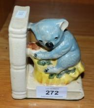 Vintage Australian pottery bookend featuring a koala on a tree on 2 books, in the style of Grace Seccombe, small chip repair to base, 10cm H