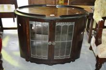 1920s walnut drink serving cabinet, pair of lead glazed doors to each side, oval shaped, on castors, originally would have had a tray top, 59cm T x 75cm W