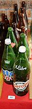Collection of 11 large soft drink bottles, 4 green