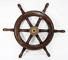 A teak and brass helm, unsigned:, 77cm diameter.