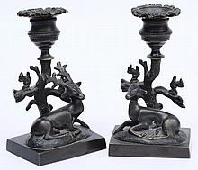 A pair of late Regency bronze candlesticks: the ur