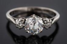 A platinum and diamond three-stone ring: with central, round old brilliant-