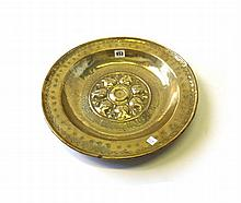 A Nuremberg brass alms dish, 16th century with raised stylized flowerheads and a band of script within a wide foliate border, 40cm diameter and another similar brass alms dish, 39.5cm diameter. (2)
