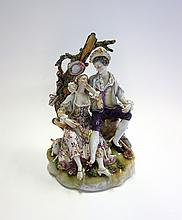 A Volkstedt porcelain figure group, late 19th century, modelled with gallant and companion under an arbour on a naturalistic base, blue painted mark to base, 25.5cm high.   Illustrated