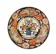 A Japanese Imari plate, Edo period, late 17th/early 18th century, painted in the centre with a basket of flowers, the border painted with flowers and panels of shishi, 28cm. diameter.  Illustrated