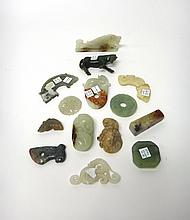 A group of fourteen Chinese jade and hardstone carvings, some in archaic style, including; a celadon jade bi disc carved with chilong; a carving of a fish; a carving of a horse; two arched pendants, huang; a jade lotus pebble carving with russet