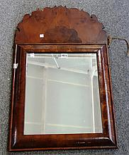 A 20th century William and Mary style walnut and yew wood oyster veneered cushion framed wall mirror, with fret carved upper frieze, 47cm wide x 87cm high.