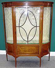 An Edwardian inlaid mahogany display cupboard, with central astragal glazed door flanked by rounded corners, on tapering square supports, 136cm wide.